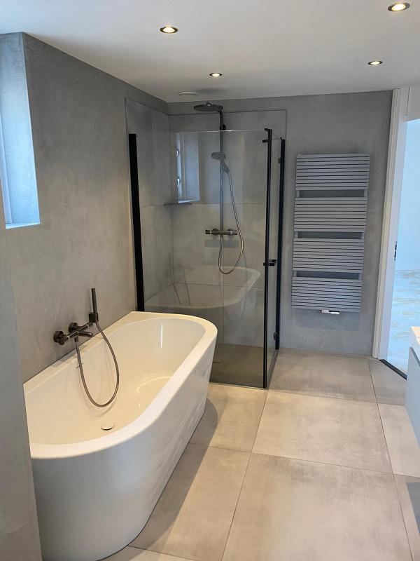 strakke betonlook badkamer met zwarte elementen